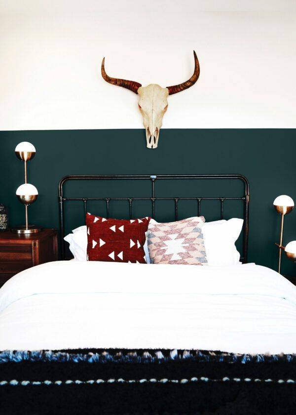 Chambre à coucher avec lit en métal et crâne accroché au mur, mis en valeur par notre vert émeraude profond AMAZON - N°2030 Peintures 1825