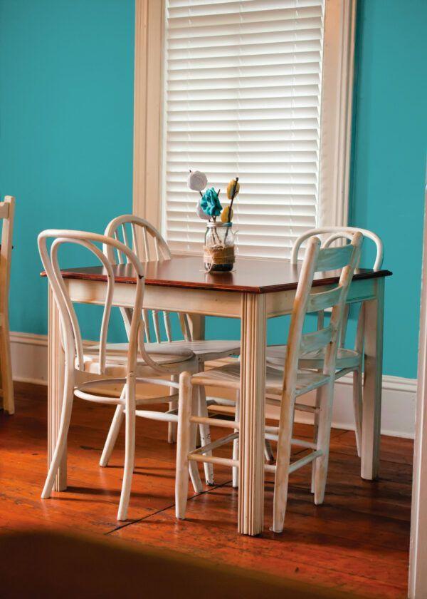 Salle à manger avec table et chaises blanches en bois, mise en valeur par notre bleu turquoise CÉLADON - N°2069 Peintures 1825
