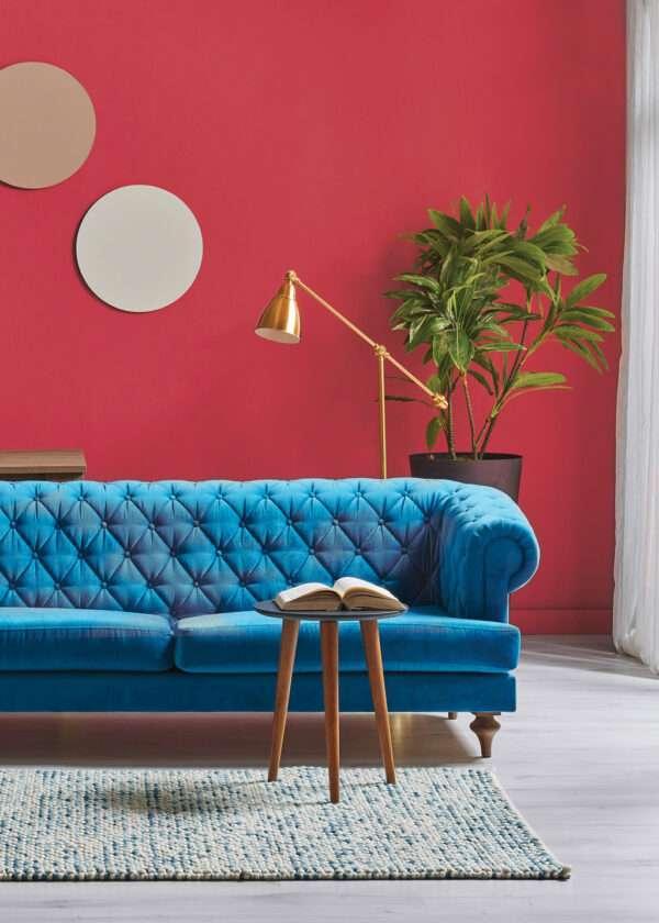 Salon avec canapé bleu vif, mis en valeur par notre rouge framboise CORAL COD - N°2048. Peintures 1825