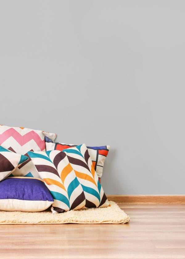 Salon avec tapis beige et coussins colorés, mis en valeur par notre gris clair NUAGE - N°1899 Peintures 1825