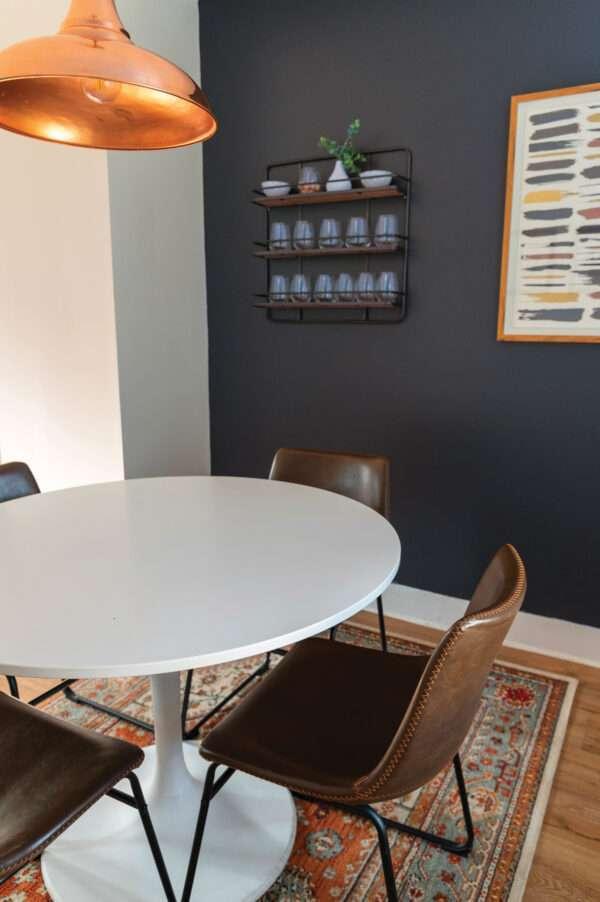 Salle à manger avec table blanche et chaises en cuir marron, mis en valeur par notre gris foncé VINYL - N°2041 Peintures 1825