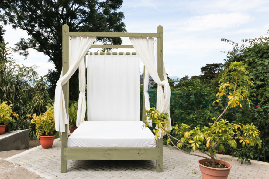 A wooden outdoor bed with white linens and privacy curtains on a brick patio at a tropical resort.