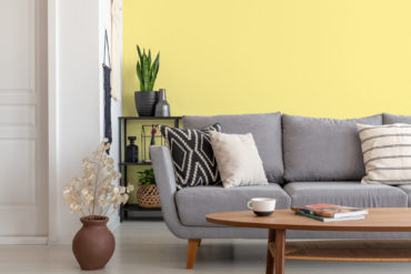 Salon avec canapé en tissu gris et table basse en bois, mis en valeur par notre jaune POP CORN - N°2019 Peintures 1825