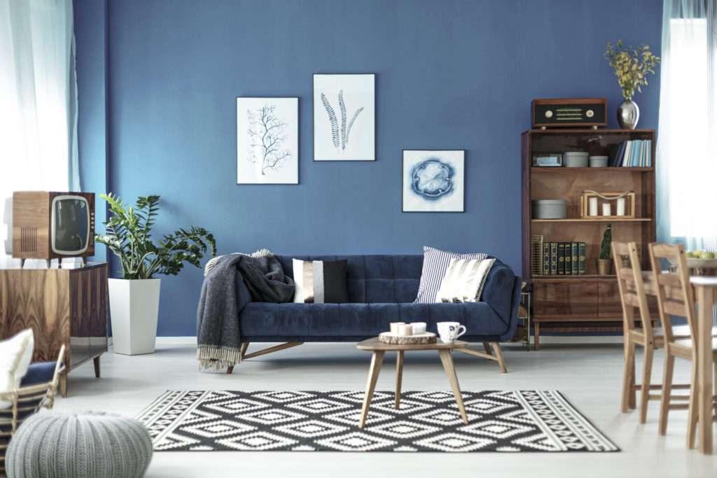 Salon avec canapé en velours bleu et meubles rétro en bois, mis en valeur par notre bleu JÄRVI - N°2077 Peintures 1825