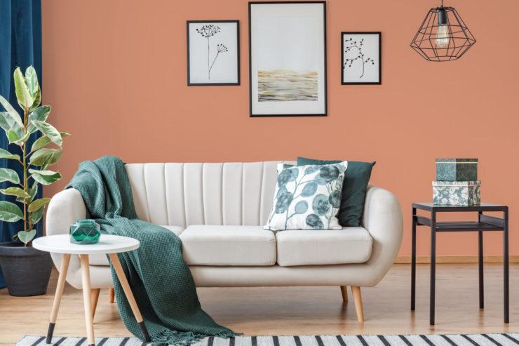 Salon avec canapé en tissu blanc et plaid vert émeraude, mis en valeur par notre brun orangé TOMETTE - N°1889 Peintures 1825