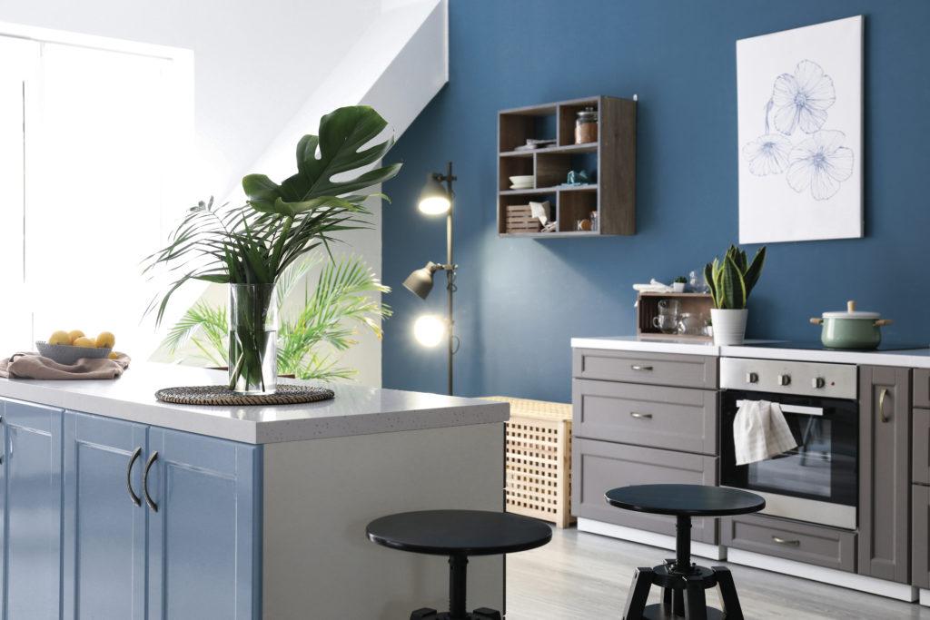 Le bleu profond JÄRVI - N°2077 appliqué sur les murs et placards d'une cuisine ouverte. Peintures 1825