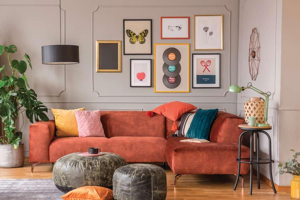 Salon avec canapé en velours rouge et tableaux muraux, mis en valeur par notre beige chaud KARITÉ - N°2028. Peintures 1825
