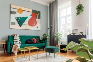 Salon moderne avec canapé en velours vert et table dorée, mis en valeur par notre teinte gris clair PÉLICAN - N°1985. Peintures 1825